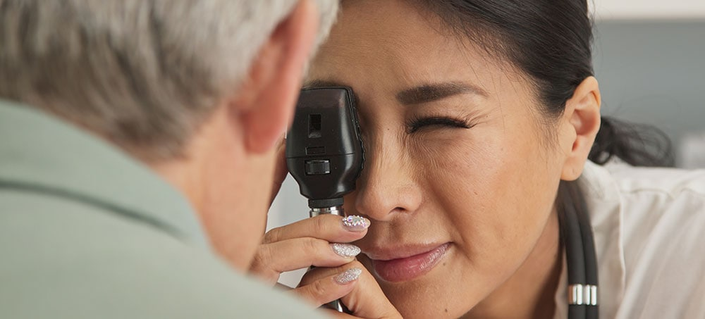 Eye exam with ophthalmoscope for retinopathy