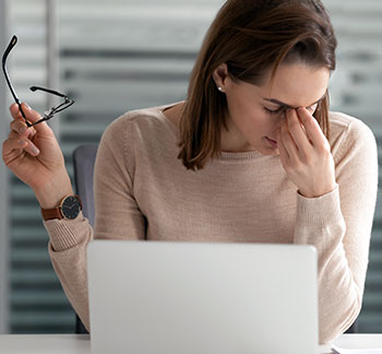 Woman with dry eyes in front of computer